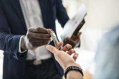 Agent nieruchomości wręcza domowego klucz klient fotografia stock