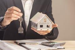 Agent nieruchomości wręcza nad domowymi kluczami Fotografia Royalty Free