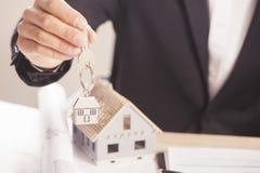 Agent nieruchomości wręcza nad domowymi kluczami Obraz Stock