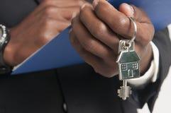 Agent nieruchomości wręcza nad domowymi kluczami Obrazy Stock
