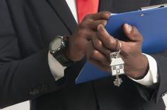 Agent nieruchomości wręcza nad domowymi kluczami Obrazy Royalty Free