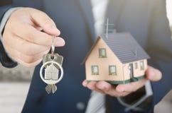 Agent nieruchomości z domowymi kluczami i dom miniaturą Fotografia Royalty Free
