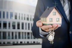 Agent nieruchomości z domowymi kluczami i dom miniaturą obrazy stock