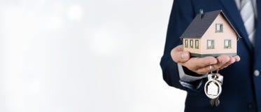 Agent nieruchomości z domowymi kluczami i dom miniaturą Fotografia Stock