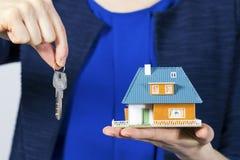 Agent nieruchomości z kluczem i dom modelujemy na ręce Obrazy Stock