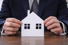 Agent nieruchomości z papieru cięciem dom przy tabl Fotografia Royalty Free