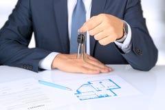 Agent nieruchomości daje domowemu kluczowi Plan kontrakt i mieszkanie behind Zdjęcia Royalty Free