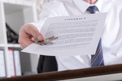 Agent nieruchomości daje kluczom z kontraktem Obrazy Stock