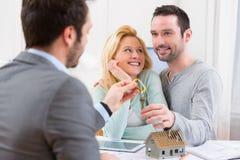 Agent nieruchomości dostarcza klucze nowy dom potomstwo para Zdjęcia Stock