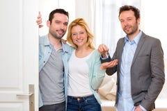 Agent nieruchomości dostarcza klucze nowy dom potomstwo para Obrazy Royalty Free