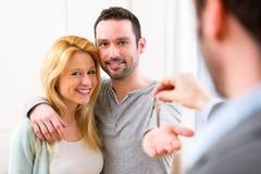 Agent nieruchomości dostarcza klucze nowy dom potomstwo para Fotografia Royalty Free