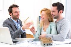Agent nieruchomości dostarcza klucze nowy dom potomstwo para Obraz Royalty Free