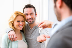 Agent nieruchomości dostarcza klucze nowy dom potomstwo para Fotografia Stock
