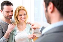 Agent nieruchomości dostarcza klucze nowy dom potomstwo para Zdjęcie Stock