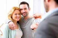 Agent nieruchomości dostarcza klucze nowy dom potomstwo para Zdjęcie Royalty Free