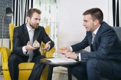 Agent nieruchomości dyskutuje z projektami i domu modelem Zdjęcia Stock