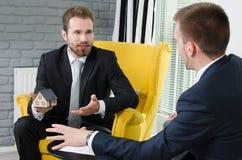 Agent nieruchomości dyskutuje z projektami i domu modelem Zdjęcie Stock
