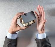 Agent nieruchomości lub deweloper trzyma dom Fotografia Royalty Free