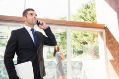 Agent nieruchomości opowiada na telefonie komórkowym Zdjęcia Royalty Free