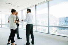 Agent nieruchomości opowiada z potencjalnymi klientami przy nowym biurem s Obraz Royalty Free