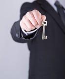 Agent nieruchomości trzyma out klucz Fotografia Stock