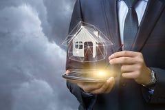 Agent nieruchomości trzyma wzorcowego dom na pastylce Obrazy Royalty Free