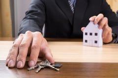 Agent nieruchomości z domów kluczami i modelem Zdjęcia Stock