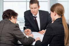 Agent signing documents with couple women Stock Image
