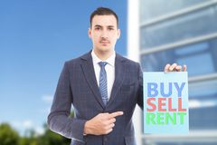 Agent pointing at buy sell rent paper sign. Real estate agent with friendly expression pointing by using index finger at buy sell rent colourful blue paper sign royalty free stock images