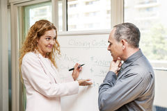 Agent presenting real estate costs. Real estate agent using flip chart with closing cost data royalty free stock photo