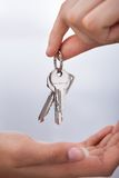 Agent's hand giving new home keys to woman Royalty Free Stock Photo