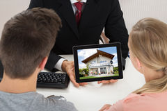 Agent Showing House On Digital Tablet To Couple Stock Image