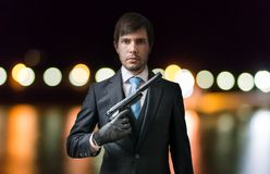 Agent or spy holds pistol in hand at night. Blurred lights in background Stock Image