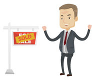 Agent standing near sold real estate sign. Stock Images