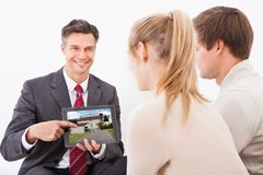 Agent with tablet pc showing house to couple Stock Photo
