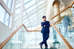 Agent on travel. Young agent talking on cellphone inside modern building Royalty Free Stock Photos