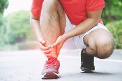 Agent wat betreft pijnlijke verdraaide of gebroken enkel Atletenagent opleidingsongeval stock afbeeldingen