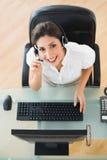 Agente alegre del centro de atención telefónica que mira la cámara mientras que en una llamada Foto de archivo