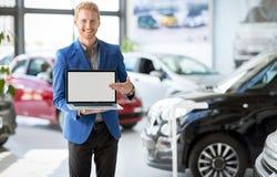 Agente alegre del coche que señala en el ordenador portátil Fotografía de archivo