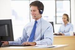 Agente amistoso Talking To Customer del servicio en centro de llamada fotografía de archivo