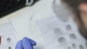 Agente che paragona il campione sospetto dell'impronta digitale all'archivio di base di dati, identificazione archivi video