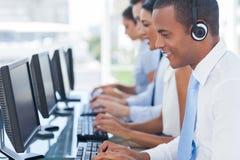 Agente che sorride mentre lavorando al suo computer Fotografie Stock Libere da Diritti