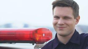 Agente da polícia amigável que olha à câmera e à proteção do sorriso, da lei e da ordem video estoque