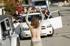 Agente da polícia Arresting Young Man Fotografia de Stock