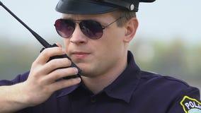 Agente da polícia determinado que comunica-se no Walkietalkie, trocando a informação vídeos de arquivo