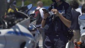 Agente da polícia fêmea que está ao lado do velomotor, verificando o telefone celular no dever filme