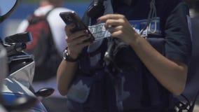 Agente da polícia fêmea que usa o telefone celular na rua, ocupação perigosa video estoque