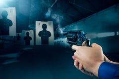 Agente da polícia que ateia fogo a uma arma em uma escala de tiro/luz dramática Imagem de Stock Royalty Free