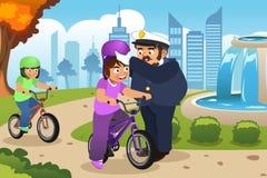 Agente da polícia Putting no capacete em uma criança que monta uma bicicleta Fotografia de Stock