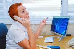 Agente de bolsa hermoso de la muchacha que habla en el teléfono en la oficina fotografía de archivo